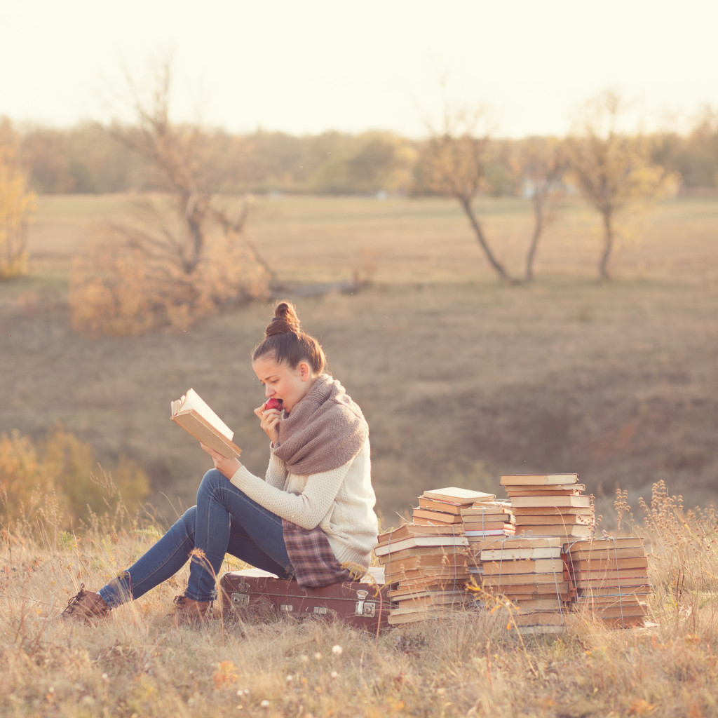 Well-read girl with many books and suitcase outdoors